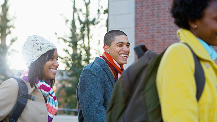 Three visiting students laugh on their way to the campus.